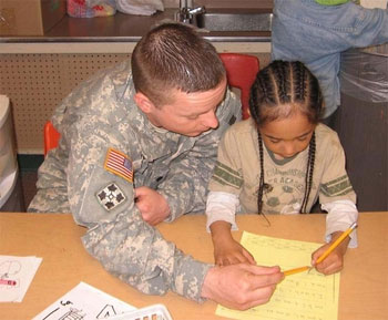 A soldier works with a kindergarten student at Chester Valley Elementary School in Anchorage, Alaska.