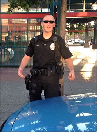 Seattle Police Department officer John Marion giving a 'Come at me, bro' gesture, photo by Dominic Holden