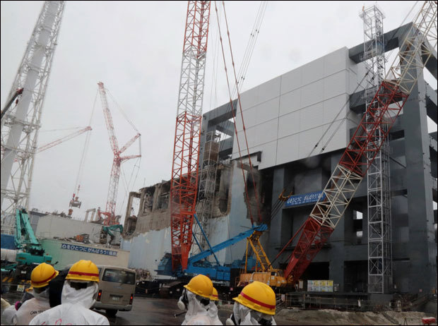 Reporters and Tokyo Electric Power Co workers look up the unit 4 reactor building during a media tour at TEPCO's Fukushima Dai-ichi nuclear plant in the town of Okuma, Fukushima prefecture in Japan on June 12, 2013. (AFP Photo / Noboru Hashimoto)