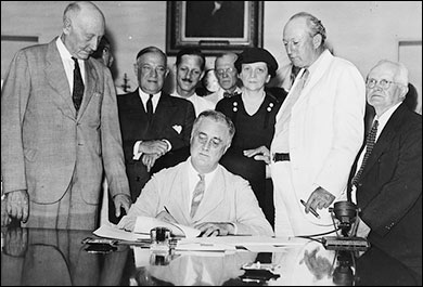 Franklin D. Roosevelt signs into law the Social Security Act on August 14, 1935.