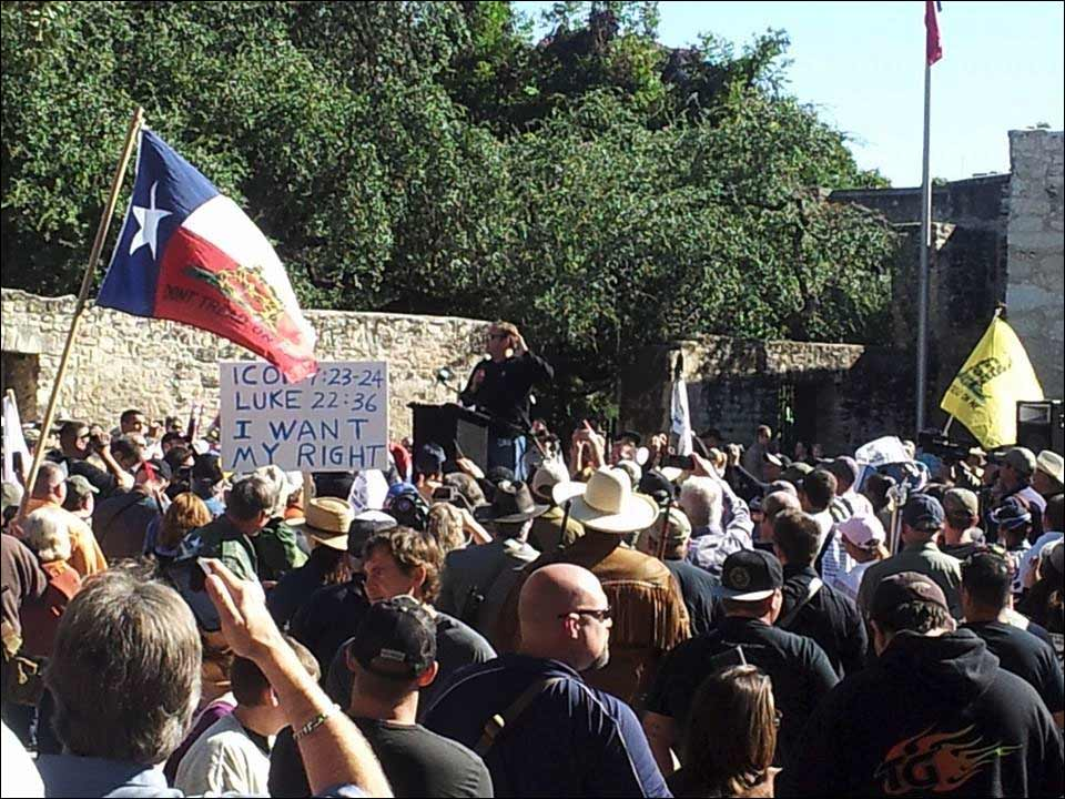 Alex Jones speaks to crowd carrying rifle. / image via Come and Take It San Antonio Facebook.