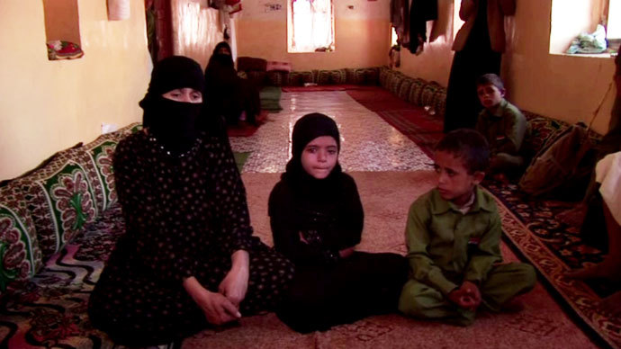 Um Salim al-Qawli, the mother of 20-year old Salim, sits with Ali's three children. They grieve for her son and their father. Screenshot from RT video