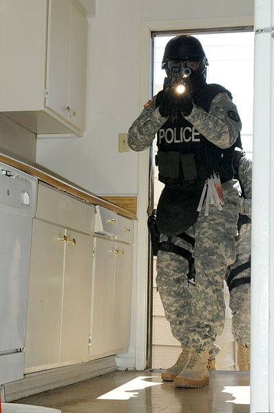 A military police officer with the Special Reaction Team, 178th Military Police Detachment, 89th Military Police Brigade, raids a house in Wainwright Village during a new training exercise at Fort Hood, Texas, March 5, 2013.