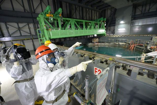 In this file photo, Fukushima Governor, Yuhei Sato (in orange helmet), inspects the spent fuel pool in the unit 4 reactor building of Tokyo Electric Power Co. (TEPCO) Fukushima Dai-ichi nuclear power plant, on October 15, 2013. - AFP