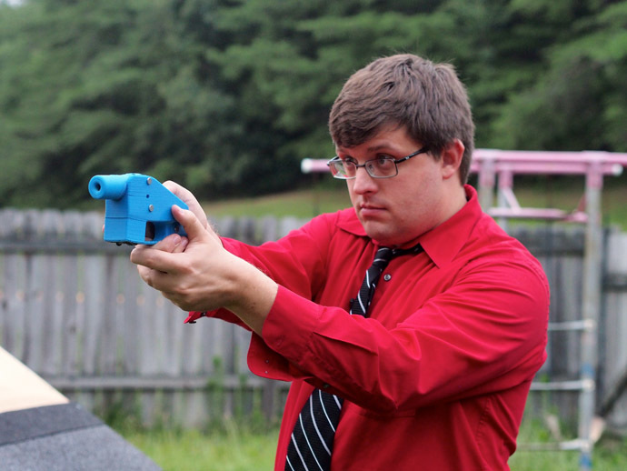 Software engineer Travis Lerol takes aim with an unloaded Liberator handgun in the backyard of his home on July 11, 2013. (AFP Photo/Robert MacPherson)