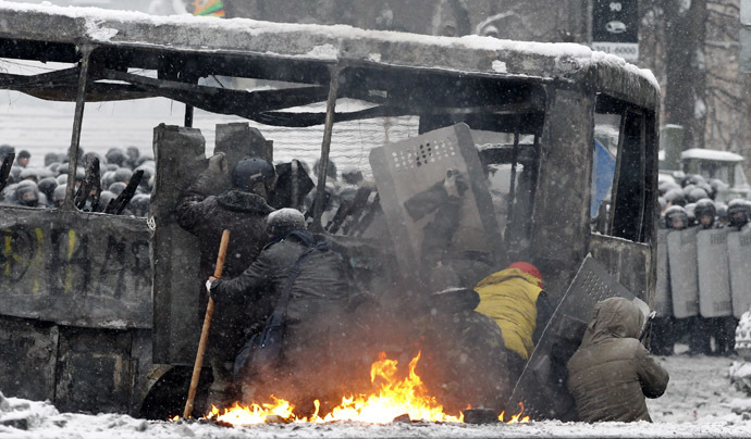 Pro-European protesters take cover behind a burnt bus during clashes with riot police in Kiev January 22, 2014. (Reuters/Vasily Fedosenko)