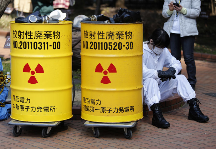 An anti-nuclear protester wearing protective suit sits next to mock drums labelled as radioactive waste from Kansai Electric Power Co's Ohi nuclear power plant (L) and Tokyo Electric Power Co's (TEPCO) Fukushima nuclear power plant, before a march in Tokyo March 9, 2014.(Reuters / Yuya Shino)