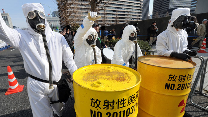 People wearing protective suits and masks shout slogans next to mock drums of nuclear waste from the Fukushima Daiichi nuclear power plant, during a march denouncing nuclear power plants in Tokyo on March 9, 2014. (AFP Photo / Toru Yamanaka)