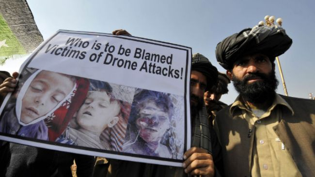 Pakistani tribesmen show a placard of the victims of a US drone strike. (File photo), via PressTV.ir