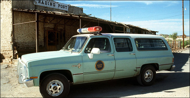 English: A. U.S. Border Patrol vehicle used in drug enforcement operations is parked in front of a trading post in a small Texas town. / 1990